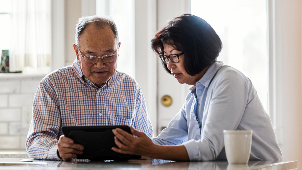 couple looking at tablet assessing health care costs