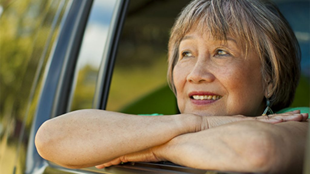 Elderly woman looking outside the window while inside a vehicle